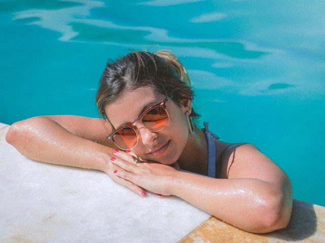 mladá dívka opřená o obrubu bazénu