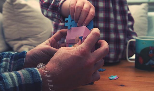 ruce drží nějaké kostky, dítě na ně vkládá další dílky