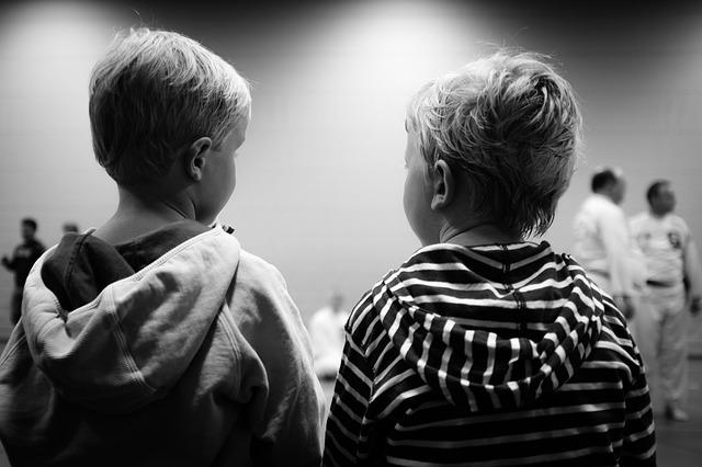 černobílá fotografie, dvě kluci sedí zády